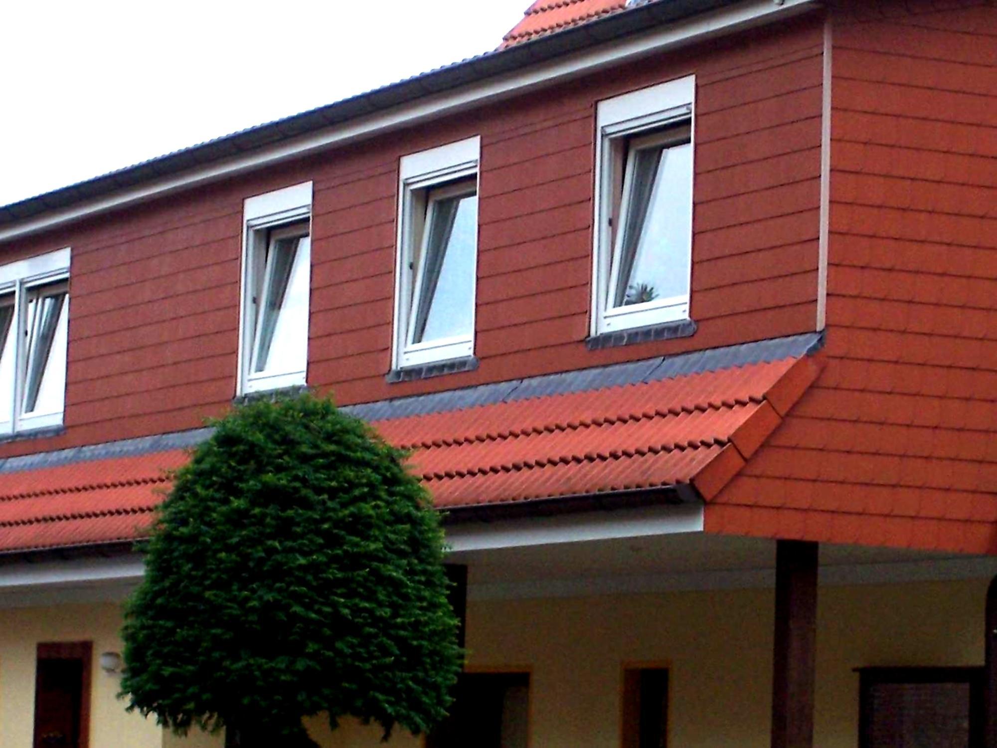 fassade eines reihenhauses mit schindeln in ziegelrot schindeln dachziegel fassadenplatten aus. Black Bedroom Furniture Sets. Home Design Ideas